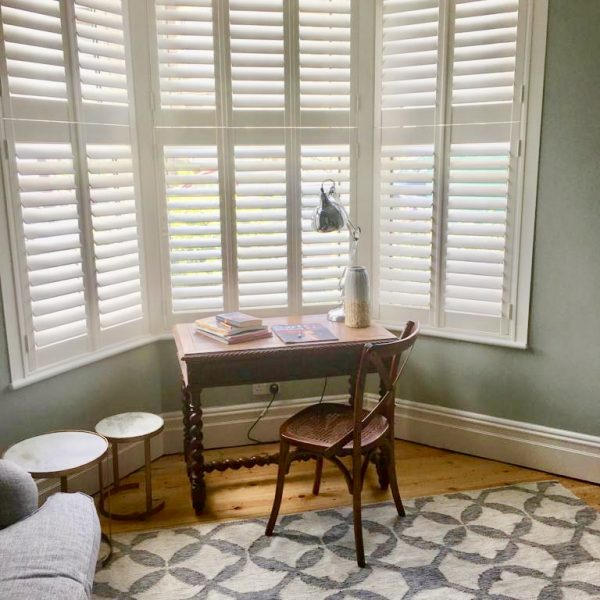 Bay window shutters in the living room with a tier on tier design
